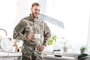 army soldier holding coffee cup in kitchen smiling