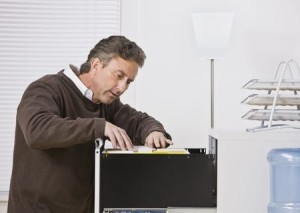 Middle aged man looking through a file cabinet